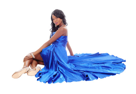 sitting pretty: A beautiful African American woman in a blue evening dress sitting on the floor