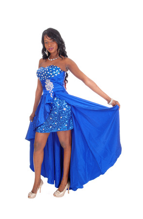 african american woman: A lovely African American woman in a long blue evening dress with curly black hair standing