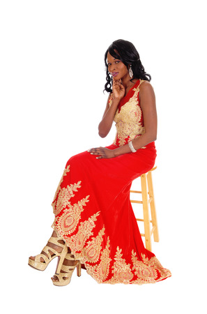 red evening: A lovely African American woman sitting in a red evening dress whit gold embroidery Stock Photo