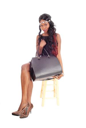 modelos negras: Una imagen del retrato de una mujer afroamericana con el pelo rizado negro largo rojo que se sienta en la silla Foto de archivo