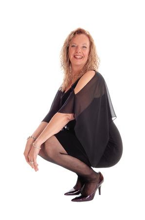 Una bella donna bionda e felice in un abito nero accucciato sul pavimento