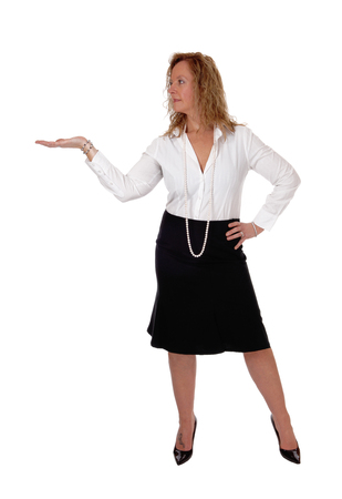 A middle age business woman in a black skirt and white blouse standing with a outstretched hand