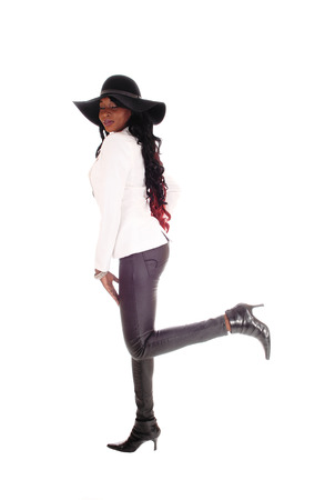 leather pants: A young slim African American woman in tight leather pants, white jacket  and black hat standing isolated for white background. Stock Photo