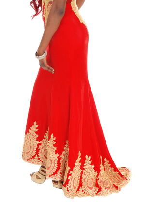 A lovely African American woman standing in a red evening dress whit gold embroidery bottom body part, isolated for white background. Banco de Imagens