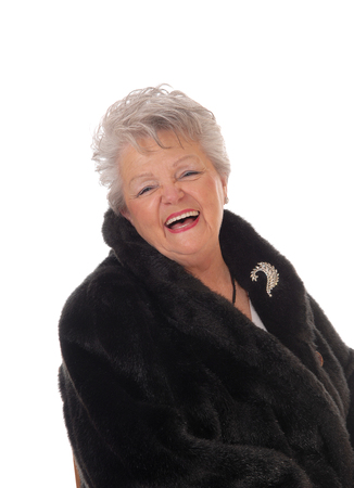 winter woman: A lovely senior woman in a black fur coat laughing with her mouth open, isolated for white background.