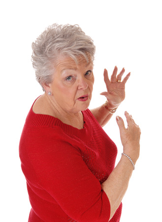 A closeup image of a very scared and surprised senior woman in a redsweater and gray hair, isolated for white background. Banco de Imagens