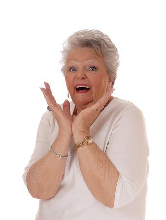 Mujer mayor que emite de salido con la boca abierta y las manos en su cara, aislado de fondo blanco. Foto de archivo - 55146609