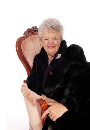 A lovely senior woman in a black fur coat laughing, sitting in a pink armchair, isolated for white background.