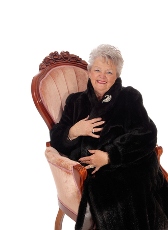 manteau de fourrure: A lovely senior woman in a black fur coat smiling, sitting in a pink armchair, isolated for white background. Banque d'images