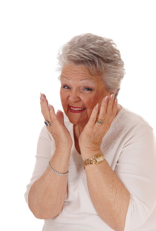 gray haired: A gray haired senior citizen woman with her hands on her face, smiling and is very happy, isolated for white background.
