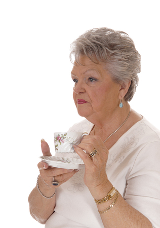 A lovely senior woman in a white sweater and short gray hair holding a