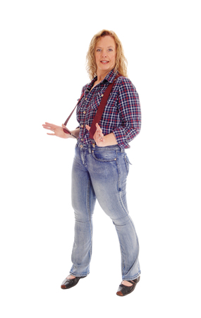 suspender: A middle age lovely woman standing isolated for white background in  jeans and checkered shirt holding her red suspender. Stock Photo