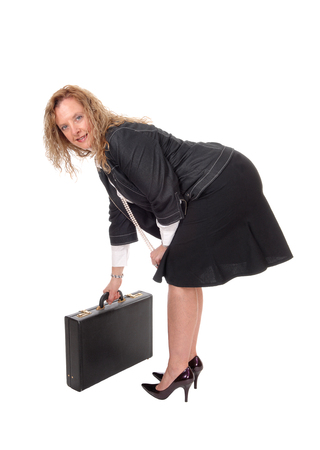Una donna d'affari chinandosi raccogliendo la sua valigetta in tacchi alti, guardando nella telecamera, isolato per sfondo bianco. Archivio Fotografico
