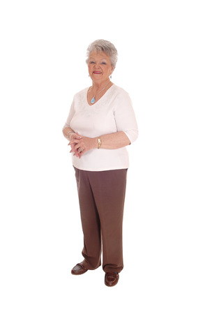 A senior citizen woman standing full length in brown pants and sweater,