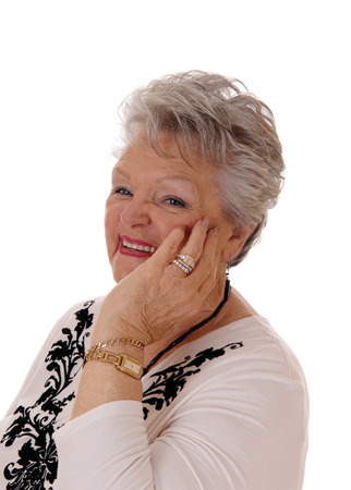 the seventies: A lovely senior woman in her seventies holding her hand on her face and smiling, isolated for white background.
