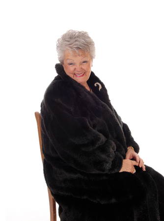 A lovely senior woman in a black fur coat smiling, sitting on a chair, isolated for white background.
