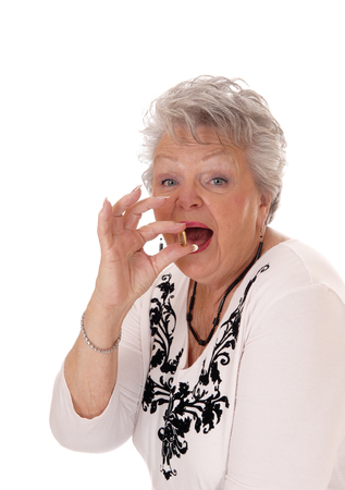 vitamin pill: A beautiful senior woman in her seventies holding a vitamin pill, in closeup isolated for white background.