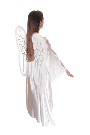 An angel in a long white satain dress with wings and long brown hairstanding in profile with arms down, isolated for white background.