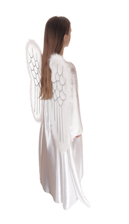 satin dress: An angel in a long white satin dress with wings and long brown hairstanding in profile isolated for white background.