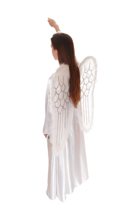 satin dress: An angel in a long white satin dress with wings and long brown hairstanding in profile with arm raised, isolated for white background.