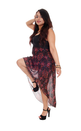 east indian: An young East Indian woman standing in a dress, lifting one leg, in a long dress and high heels, isolated for white background.