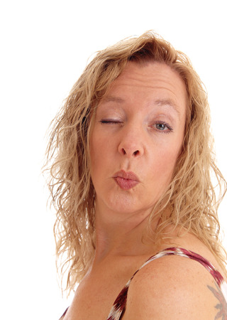 eye closed: A blond middle aged woman blowing a kiss with one eye closed, isolated for white background.