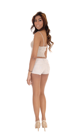 A tall gorgeous woman standing from the back, looking over her  shoulder in beige shorts, isolated for white background.