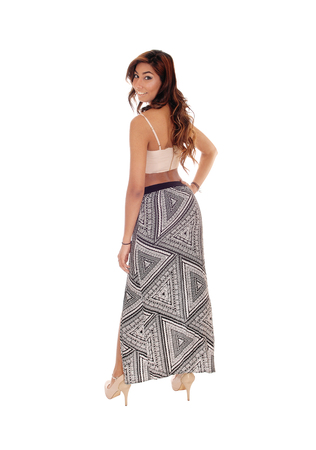 long skirt: A beautiful young woman in a long skirt and short top, standing from the back, looking over shoulder, isolated for white background.