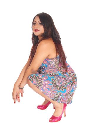 Una bella donna indiana orientale in un abito colorato accovacciata sul pavimento in studio, isolato per sfondo bianco.