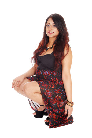 east indian: A lovely young East Indian woman in a long dress crouching on the floor in the studio, isolated for white background.