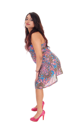 bending down: A beautiful young East Indian woman standing full length in a colorful summer dress, bending down, isolated for white background.