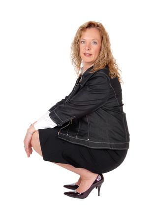 Una hermosa mujer rubia en cuclillas en el suelo en una falda y chaqueta azul marino negro, aislado de fondo blanco.