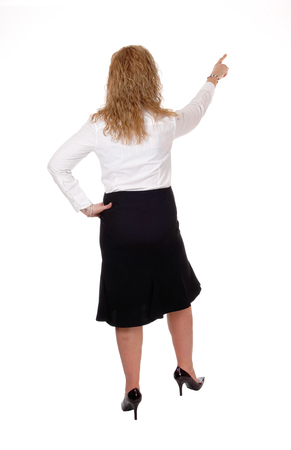 business for the middle: A middle age business woman in a black skirt and white blouse standing from back with a outstretched hand, isolated for white background. Stock Photo