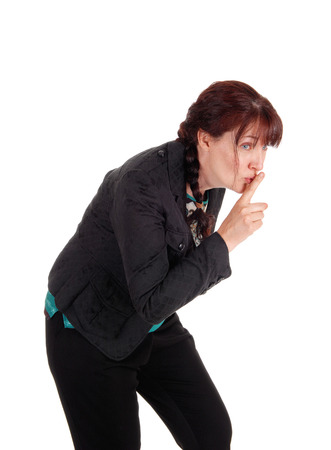 bend over: A lovely middle age woman walking bend over with one finger over her mouth, isolated for white background. Stock Photo