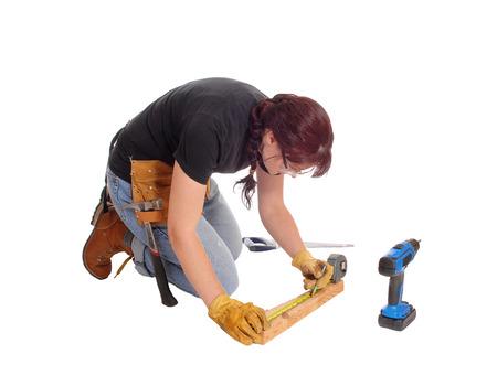 mujer arrodillada: Una mujer de mediana edad de rodillas en el suelo y trabajar con algunas herramientas de medición, aislado de fondo blanco. Foto de archivo