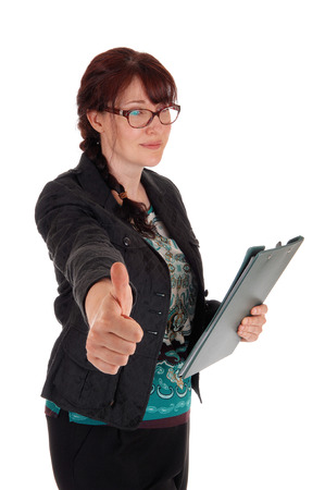 thump: A Caucasian business woman standing with her clipboard in her hand and showing her thump up, isolate for white background.