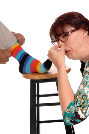discussed: A discussed woman holding her nose closed from the smell of her husbands socks, isolated for white background. Stock Photo