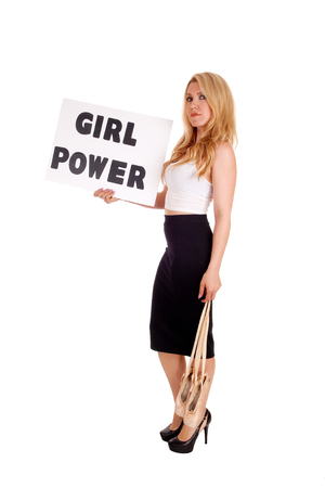 A lovely young blond woman standing in a black skirt and ballet shoe in  her hand holding a sign girl power, isolated for white background.