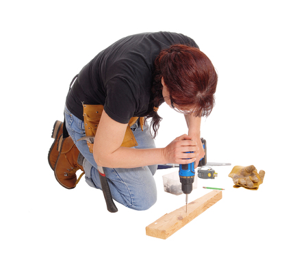 woman kneeling: A middle age woman kneeling on the floor and working with some tools drilling in wood, isolated for white background. Stock Photo