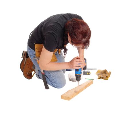mujer arrodillada: Una mujer de mediana edad de rodillas en el suelo y trabajar con algunas herramientas de perforación en madera, aislado de fondo blanco.