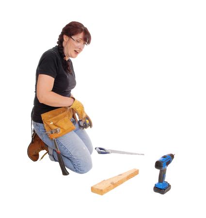 mujer arrodillada: Una mujer de mediana edad de rodillas en el suelo y trabajar con algunas herramientas, aislado de fondo blanco.