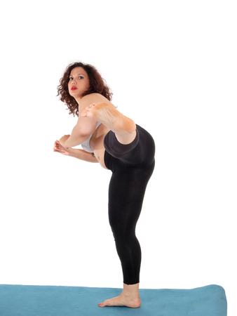 An exercising young woman in black pants standing on a blue mat, kicking with her leg, isolated for white background.