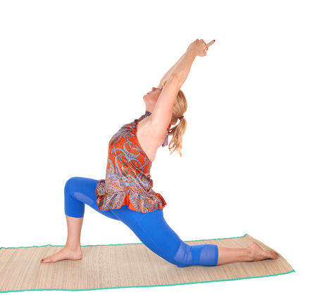 A pretty woman with blond hair stretching on a matt with a yoga pose, isolated for white background.