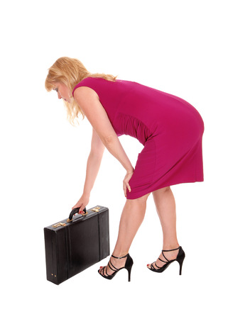 A business woman in a red dress bending down picking up her brief-