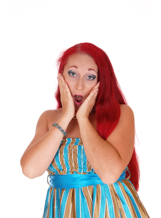 thirties: A pretty woman in her thirties with long red hair holding her face is shocked what she sees, isolated for white background. Stock Photo