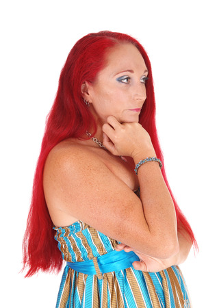 thirties: A portrait image of a woman in her thirties, holding her hand under her chin with long red hair, isolated for white background. Stock Photo