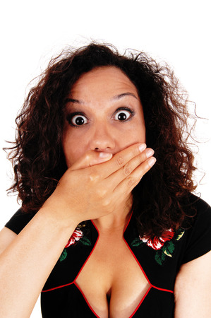 eyes wide: A beautiful young woman with curly brunette hair is frightened, holding her hand over her mouth and her eyes wide open. Stock Photo
