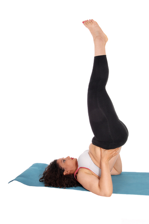 yoga pants: A young woman lying on the floor lifting up her legs in black yoga pants, isolated for white background.
