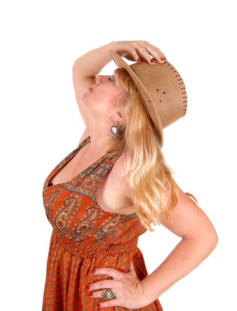 A portrait image of a pretty blond woman in a dress wearing a cowboy hat, isolated for white background.
