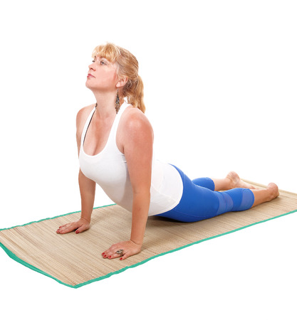 A lovely blond woman is yoga outfit lying on her stomach showing some  yoga exercises, isolated for white background. Stock Photo